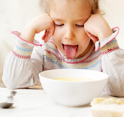 Девочка с отвращением смотрит на еду