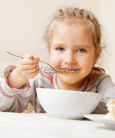 Маленькая девочка ест суп