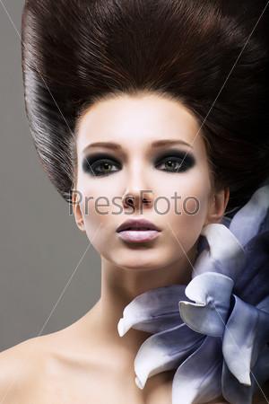 Элегантность. Молодая брюнетка с цветком. Стильный яркий макияж и прическа