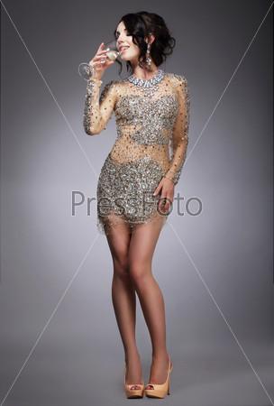 Восторг. Респектабельная женщина в вечернем платье пьет шампанское