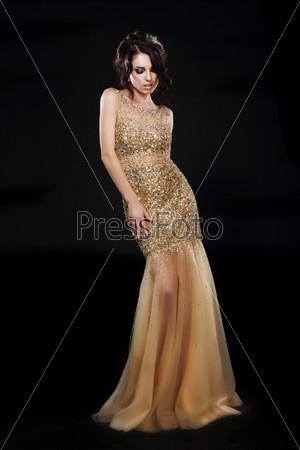 Фотография на тему Мода. Красивая фотомодель в золотистом платье на черном фоне