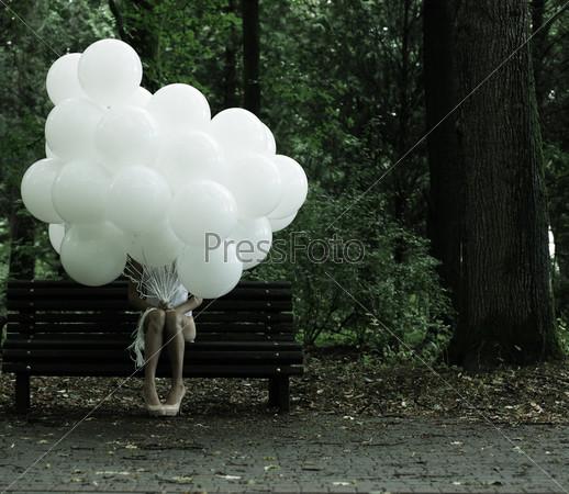 Сентиментальность. Ностальгия. Одинокая женщина с воздушными шарами сидит на скамейке в парке