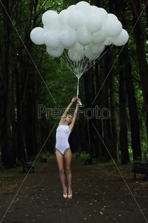 Фантазия. Стройная женщина с воздушными шарами на проселочной дороге