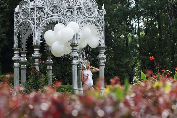 Прекрасная молодая женщина с воздушными шарами в парке