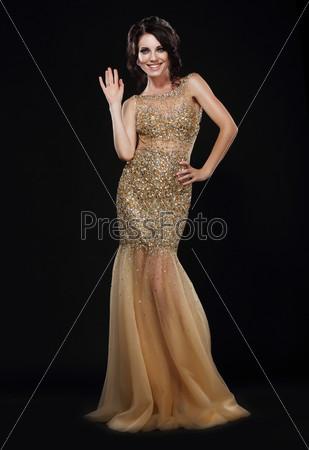 Стильность. Молодая женщина в длинном золотом платье