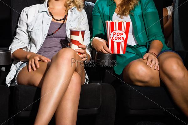 Женщины с попкорном и прохладительными напитками сидят в театре