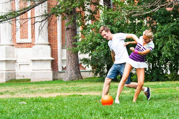 Мужчина и женщина играют в футбол в парке