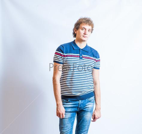 Фотография на тему Молодой счастливый улыбающийся мужчина в джинсах на сером фоне