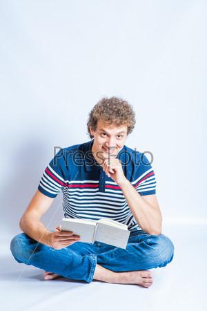 Молодой мужчина сидит на полу и читает книгу. Современный студент с вьющимися волосами