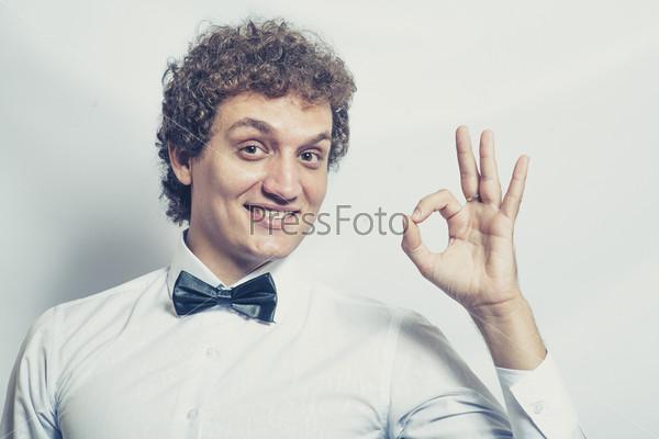 Смешной бизнесмен показывает OK на сером фоне