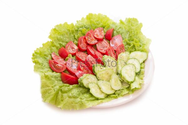 Огурцы и помидоры с солью и перцем на листе салата