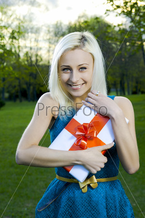 Красивая блондинка держит коробку с подарком