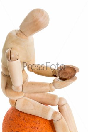 Сидящий деревянный манекен держит монету в один цент