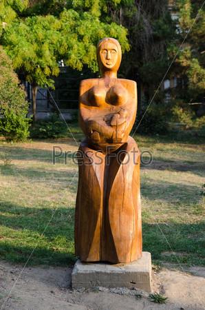 Деревянная скульптура матери с ребенком на руках