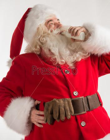 Портрет Санта-Клауса, пьющего молоко из стеклянной бутылки