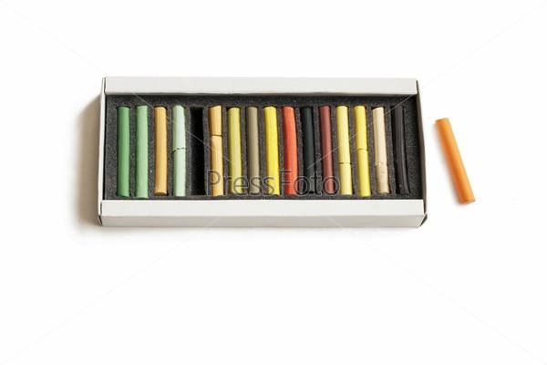 Коробка с пастельнымми карандашами на белом фоне