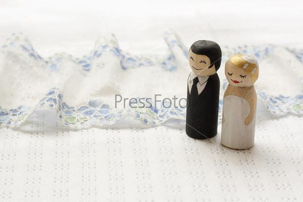 Деревянные фигурки невесты и жениха на фоне белой ткани с кружевами