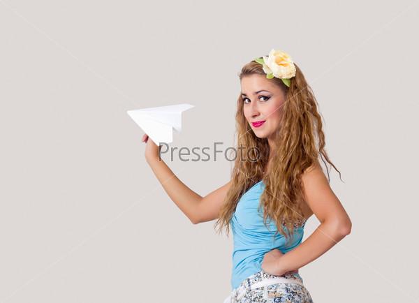 Фотография на тему Молодая женщина в стиле пин-ап с бумажным самолетом