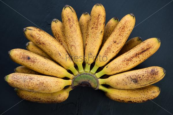 Спелые мелкие бананы на черном деревянном фоне