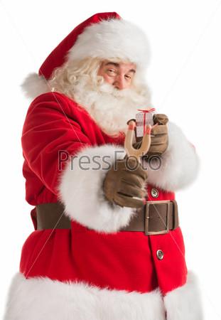 Портрет счастливого Санта-Клаус, целящегося рождественским подарком из рогатки