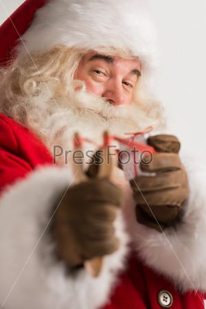 Фотография на тему Портрет счастливого Санта-Клаус, целящегося рождественским подарком из рогатки