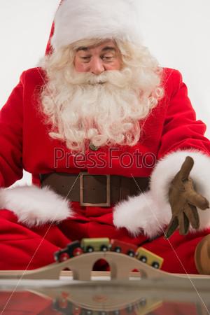 Санта-Клаус сидит и играет с игрушками