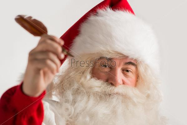Санта-Клаус держит перо в руке и пишет