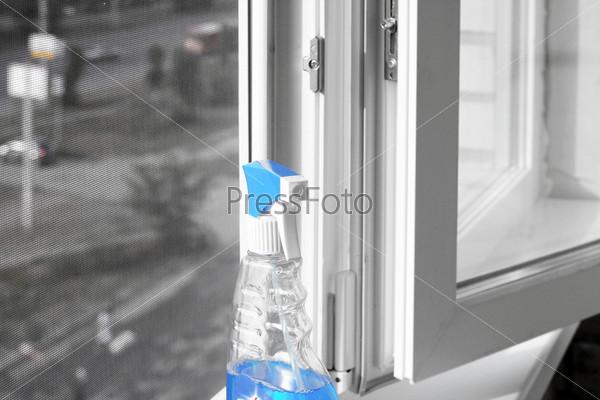 Фотография на тему Пульверизатор с чистящей жидкостью на окне