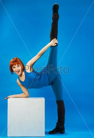 Фотография на тему Молодая рыжая женщина делает растяжку