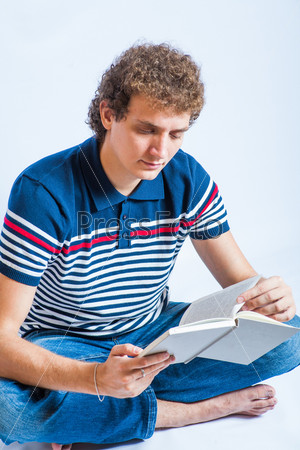 Красивый молодой студент читает книгу