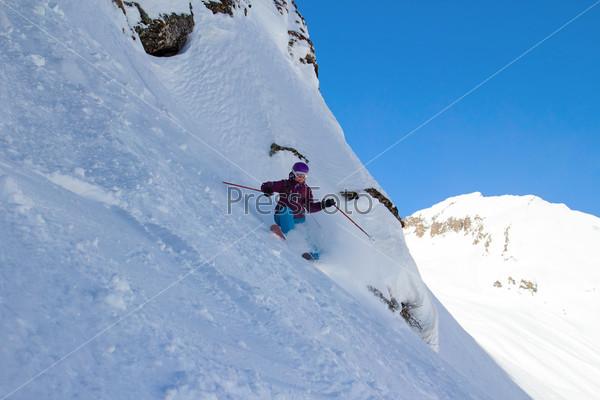 Лыжница на крутом склоне с видом на горы