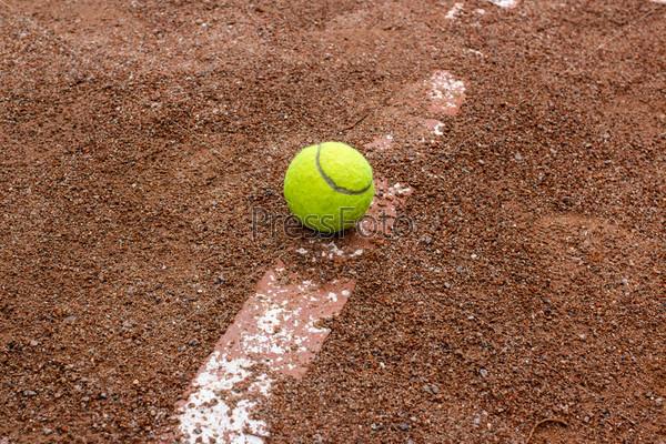 Теннисный мяч на красном корте