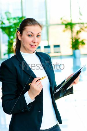 Молодая счастливая бизнес-леди с папкой и ручкой в руке
