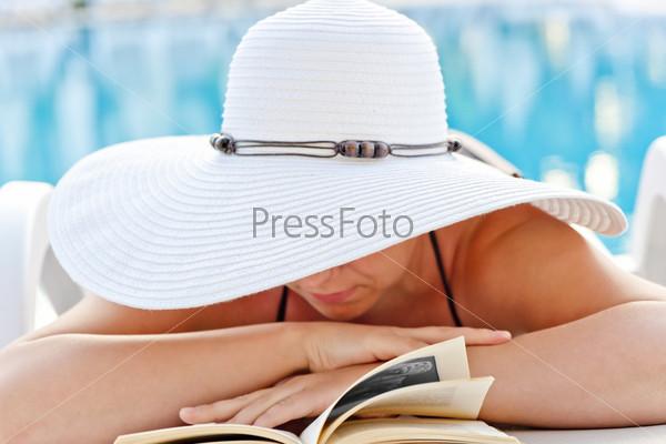 Фотография на тему Девушка в белой шляпе, читает книгу на шезлонге у бассейна