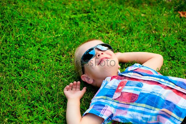 Фотография на тему Счастливый мальчик в солнцезащитных очках лежит на зеленой траве