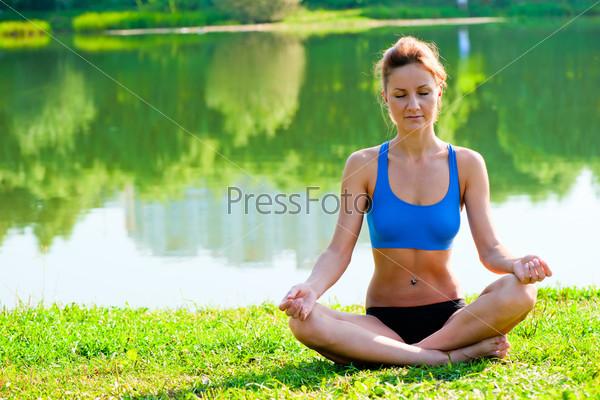Фотография на тему Подтянутая девушка в спортивной одежде медитирует в позе лотоса на берегу озера в парке