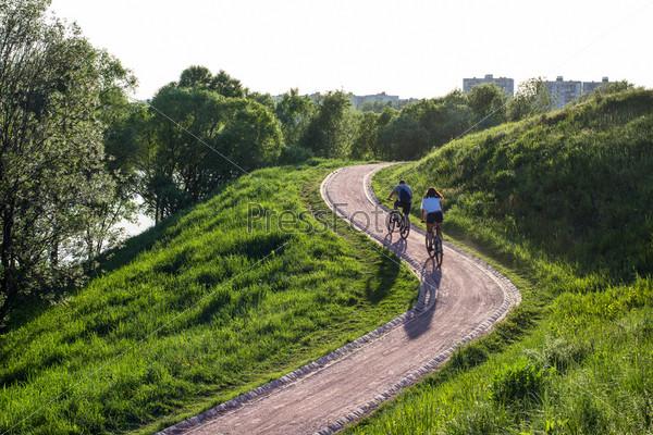Два велосипедиста едут на велосипеде на склоне холма в парке