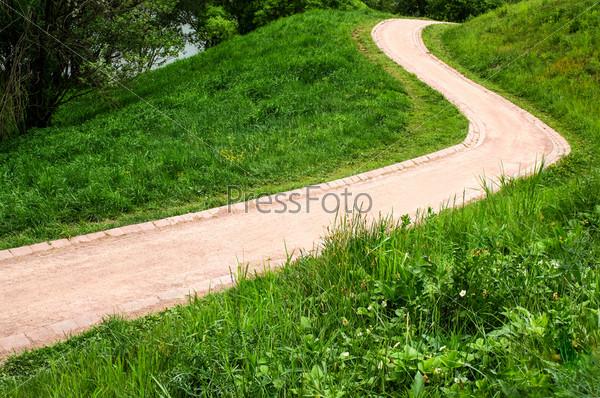 Красная извилистая тропинка в красивом зеленом парке на склоне, освещенная солнцем