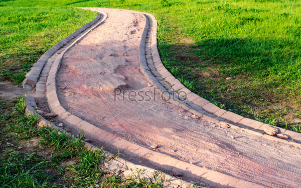 Разбитая велосипедная дорожка в зеленом парке