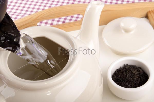 Горячая вода льется в чайник