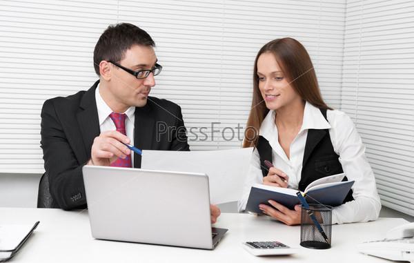 Бизнесмены, глядящие на документ в офисе