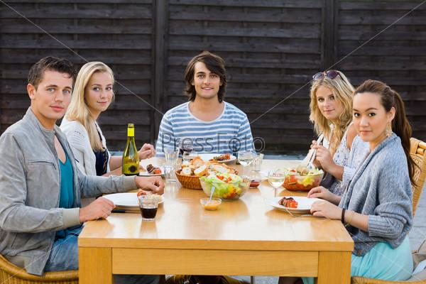 Друзья наслаждаются едой на вечеринке на природе