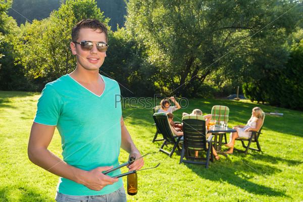 Мужчина держит щипцы и бутылку вина на садовой вечеринке