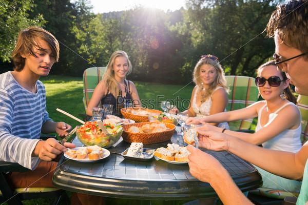 Друзья наслаждаются едой на вечеринке в саду