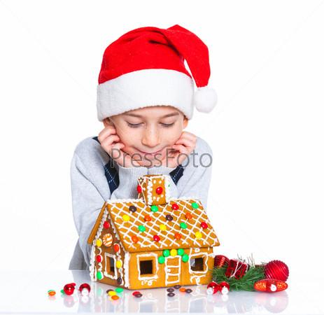 Фотография на тему Маленький мальчик в шапке Санта-Клауса с имбирным домом