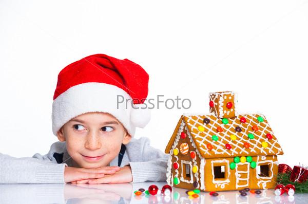 Маленький мальчик в шапке Санта-Клауса с имбирным домом