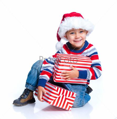 Маленький мальчик в шапке Санта Клауса с подарком
