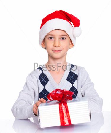Маленький мальчик в колпаке Санта-Клауса с подарком