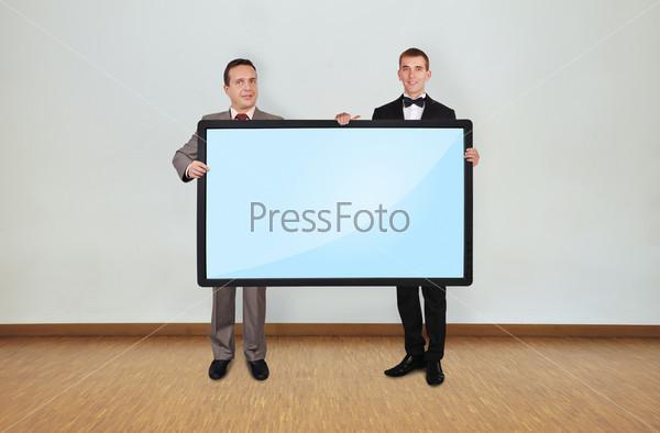 Два человека держат панель