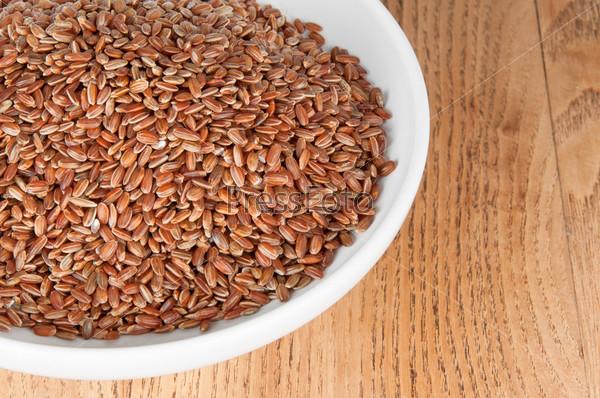 Красный рис в тарелке на столе